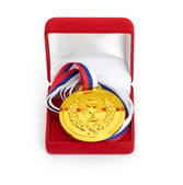 Golden medal in red gift box. isolated on white background — Stock Photo