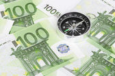 Euro bank notes and a compass — Stock Photo