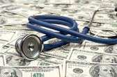 Heap of dollars with stethoscope — Stock Photo