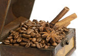 Coffee beans and cinnamon sticks inside a chest — Stock Photo