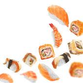 Sushi pieces flying on white background — Stock Photo
