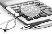 Glasses and pen on calculator — Stock fotografie