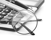 Glasses and pen on calculator — Stockfoto