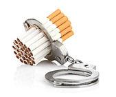Tillägg koncept med cigaretter och handfängsel — Stockfoto