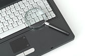 Laptop with a magnify glass — Stock Photo