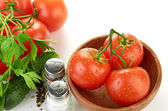 The branch of cherry tomatoes in a wooden bowl — Stockfoto