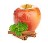 Red apple, cinnamon sticks and mint leaves — Stock Photo
