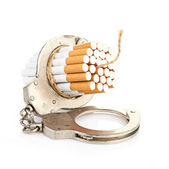 Addition concept with cigarettes and handcuffs — Stock Photo