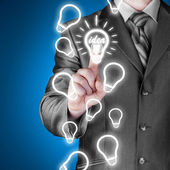 Business man touching light of idea — Stock Photo