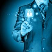 Businessman pushing virtual security button — Stock Photo