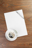 Coffee cup on paper — Stockfoto