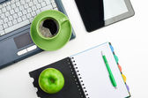 Green apple on workplace — Stockfoto