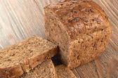 Fette di pane integrale su un tavolo di legno — Foto Stock