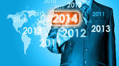 Businessman touching new year 2014 — Stock Photo
