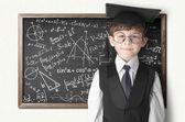 Boy near blackboard with formulas — ストック写真