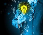 Zakenman aan licht van idee te raken — Stockfoto