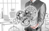 Businessman touching gears — Stock Photo