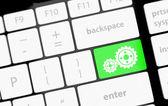 Cogwheel gear mechanism on button on white computer keyboard. — Stock Photo