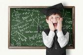 Boy near blackboard with formulas — Stock Photo