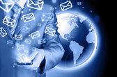 Uomo d'affari tenendo il telefono intelligente e l'invio di email — Foto Stock