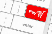 Pay key with shopping cart icon on a white keyboard — Stock Photo