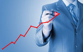Business man drawing a growing graph — Stockfoto