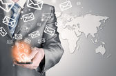 Business man holding smart phone and sending emails — Stock Photo