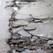 Broken pavement and pothole asphalt road after winter. — Stock Photo