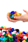 Color plastic caps in human hands — Stock Photo
