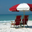 Two chairs and umbrella on white sand beach — Stock Photo