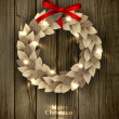 Christmas wreath made of paper leaves in eco country style decorated with red bow and sparkles — Stockvektor