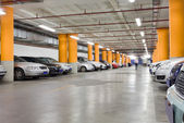 Parking garage, underground interior with a few parked cars — Stock Photo