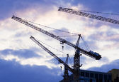 Building with elevating crane and clouds on background — Stock Photo
