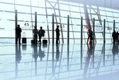 Travelers silhouettes at airport — Stock Photo