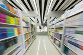 The aisles in a public library with shelves full of books — Stock Photo
