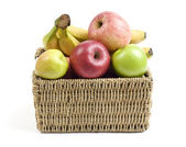 Fresh and ripe fruits in a grass crate isolated on white background — Stock Photo