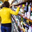 Young woman shopping in the supermarket,wine shelves — Стоковая фотография