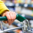 Closeup of female shopper with trolley at supermarket - ストック写真