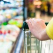 Closeup of female shopper with trolley at supermarket — Stock Photo #24504843