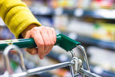 Closeup of female shopper with trolley at supermarket — Stock Photo