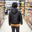 Young woman shopping in the supermarket,motion blur — Stock Photo