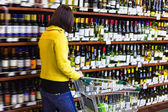 Young woman shopping in the supermarket,wine shelves — Stock Photo