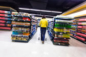 Young woman shopping in the supermarket ,motion blur — Stock Photo