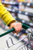 スーパー マーケットにトロリーを持つ女性の買物客のクローズ アップ — ストック写真