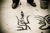 Chinese calligraphy written on the ground — Stock Photo