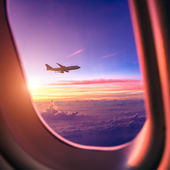 Airplane in the sky at sunrise — Stock Photo