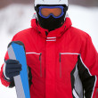 Man in a ski suit with skis — Stock Photo