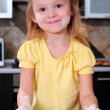 Little girl is preparing dough - Stock Photo