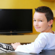 Stock Photo: Boy sitting on sofwatching TV