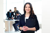 Office worker smiling, colleagues in background — Stock Photo